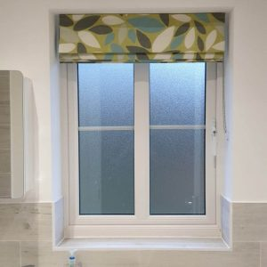 green patterned Roman blinds