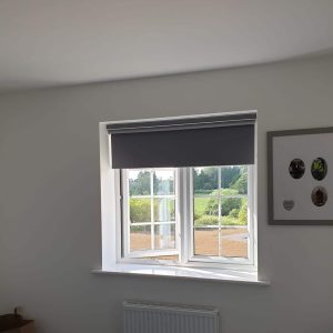 grey roller blind on open window