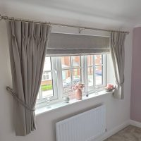 pale grey Roman blinds with matching curtains