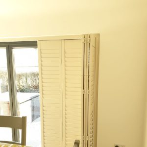 half retracted white tracked shutters