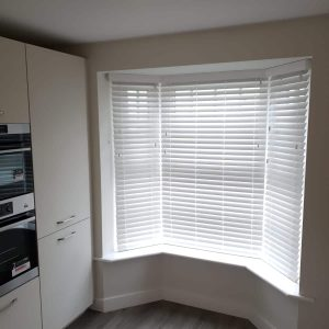 closed white Venetian blinds in a kitchen