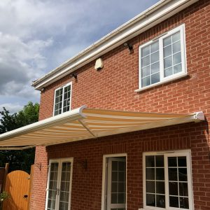 open striped awning on red brick house