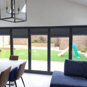 dark bi-fold door blinds in modern home