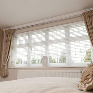 white wooden blinds in neutral bedroom