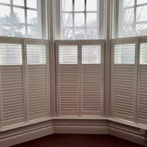 white cafe style shutters on a sash window