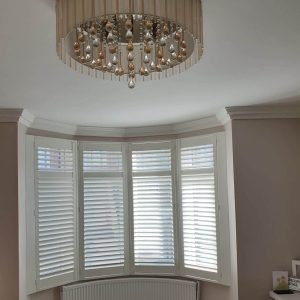 white plantation shutters in a curved bay window