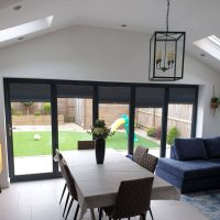bi-fold door blinds in front of dining table in modern home