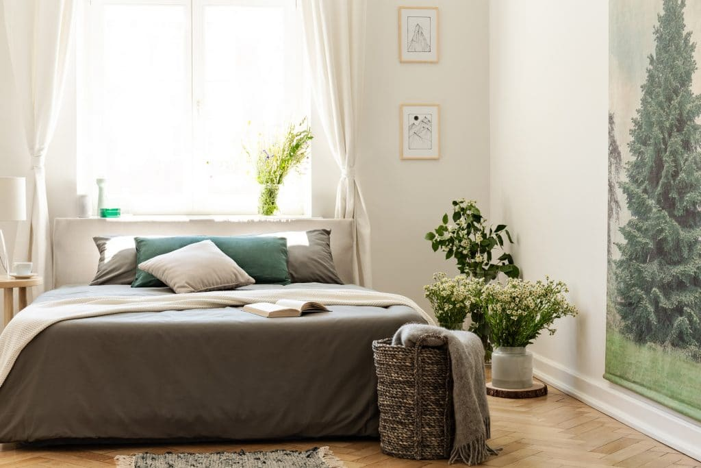 Nature bedroom interior in earth colors with a bed on a wooden floor, an evergreen tree poster on the wall and a bright window in the background.